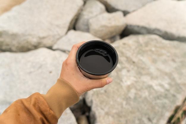 Giovane nomade o donna in cerca di avventura in giacca di pelle marrone tiene tazza di caffè americano nero o tè in tazza camper o tazza da campeggio Foto Gratuite