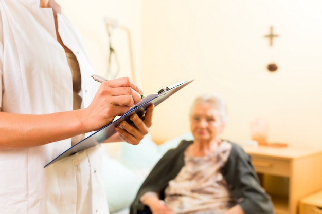 Young nurse and female senior in nursing home Premium Photo