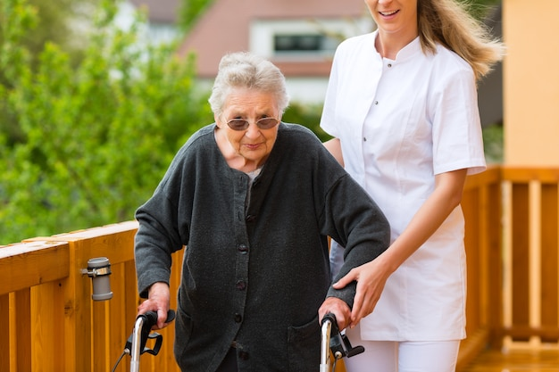 Young nurse and female senior with walking frame Premium Photo