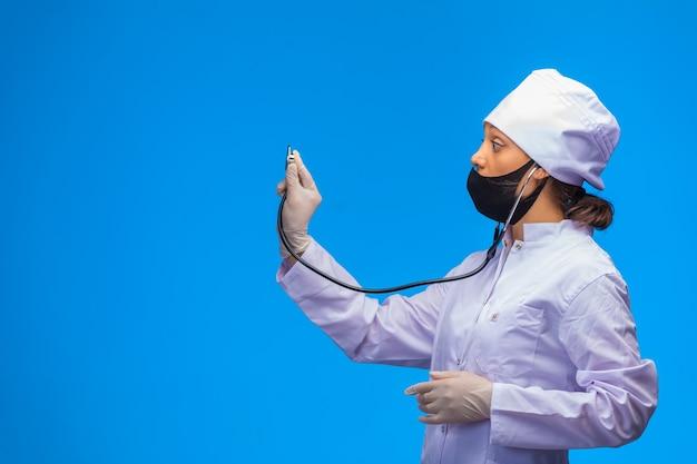 Молодая медсестра в черной маске проверяет пациента со стетоскопом на синем фоне. Бесплатные Фотографии