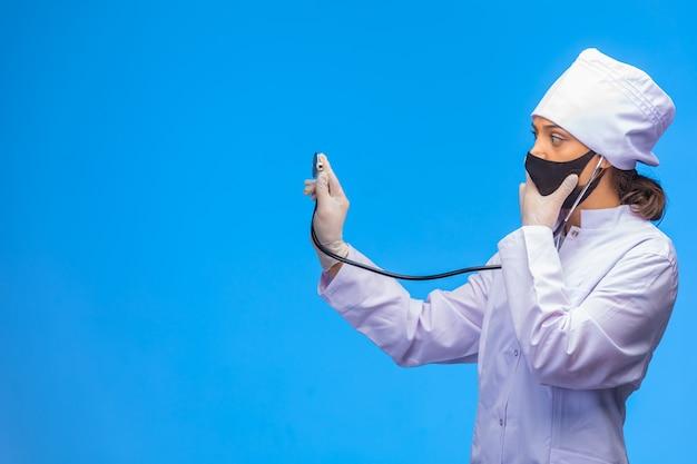 黒いマスクの若い看護婦さんが聴診器で患者をチェックします。 無料写真