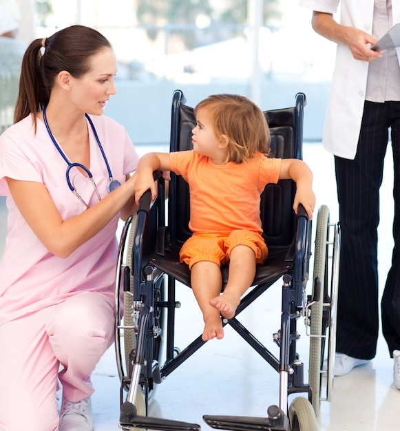 Young nurse talking to a baby in a wheelchair Premium Photo