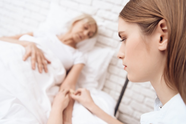 Young nursing save life elder woman in clinic. Premium Photo