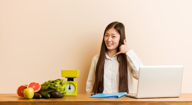 Young nutritionist chinese woman working with her laptop showing a mobile phone call gesture with fingers. Premium Photo
