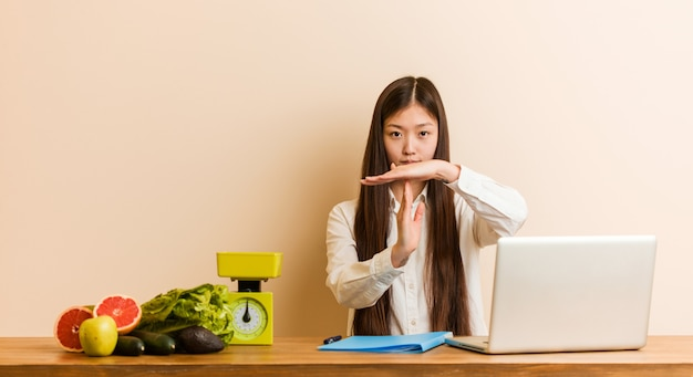 Young nutritionist chinese woman working with her laptop showing a timeout gesture. Premium Photo
