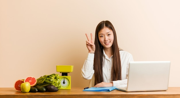 Young nutritionist chinese woman working with her laptop showing victory sign and smiling broadly. Premium Photo