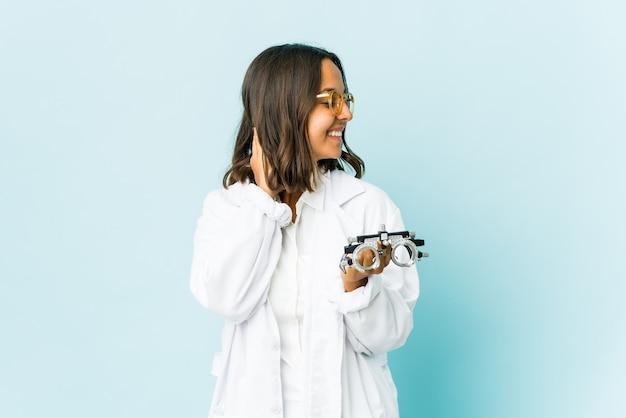 Молодая женщина-окулист чувствует себя уверенно над изолированной стеной, заложив руки за голову Premium Фотографии
