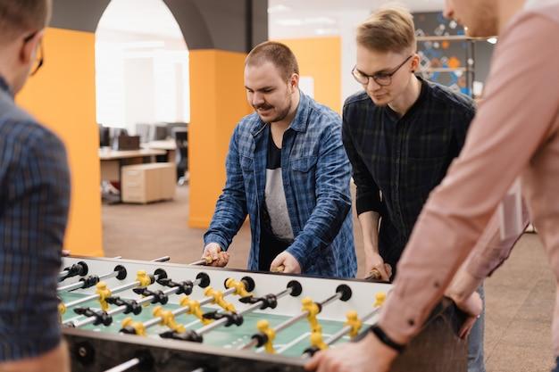 Молодые офисные работники играют в настольный футбол Бесплатные Фотографии
