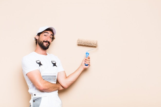 Young painter bearded man painting a wall with a paint roller Premium Photo