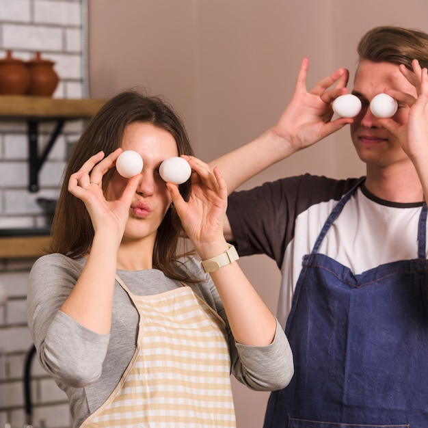 Young pair making funny faces with eggs in kitchen Free Photo