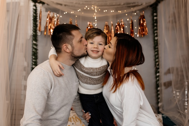 Young parents are kissing their son Free Photo