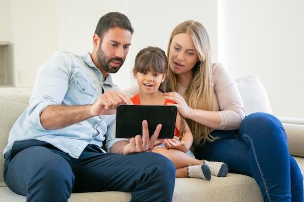 若い親カップルとかわいい娘がソファに座って、ビデオ通話や映画鑑賞にタブレットを使用しています。 無料写真