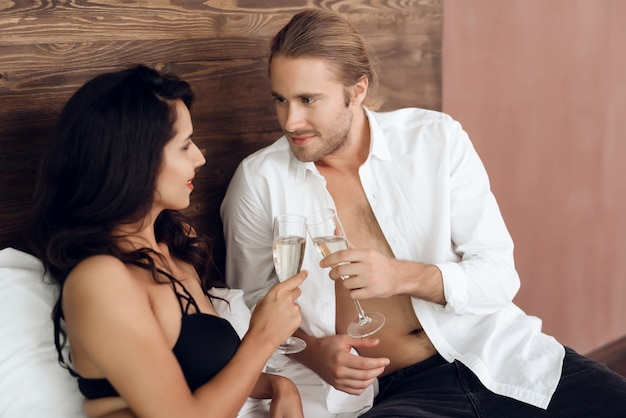 Young passionate couple cheers with glasses of champagne. Premium Photo