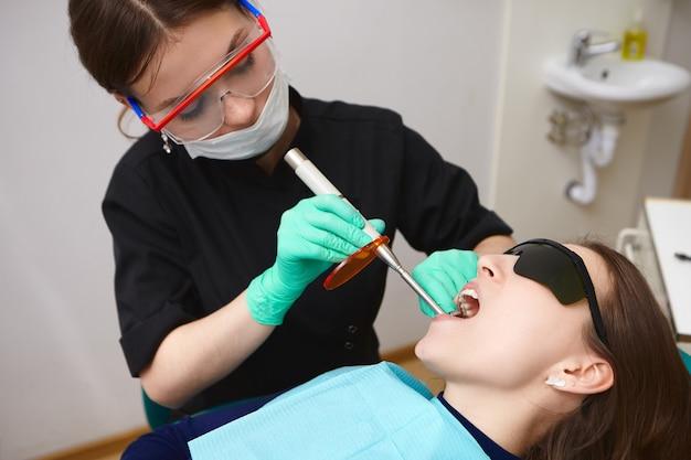 歯科硬化ライトを使用して女性の衛生士によって彼女の歯を治療されている黒いゴーグルの若い患者 無料写真