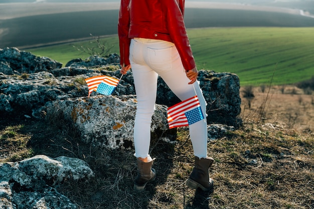 Young patriotic woman with american flag on top of mountain Free Photo
