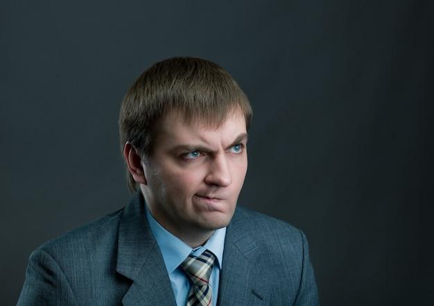 Молодой задумчивый бизнесмен на черном Premium Фотографии