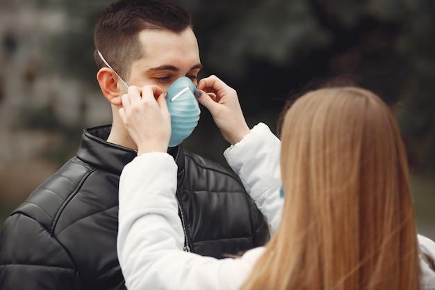 若者は使い捨てマスクを外に広げています 無料写真