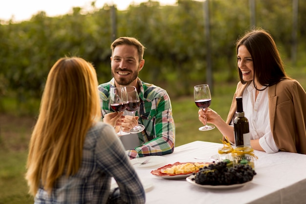 Young people by the table in the vineyard Premium Photo