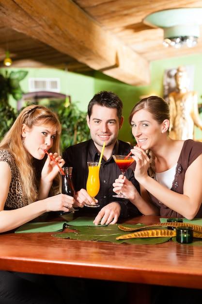 Молодые люди пьют коктейли в баре или ресторане Premium Фотографии