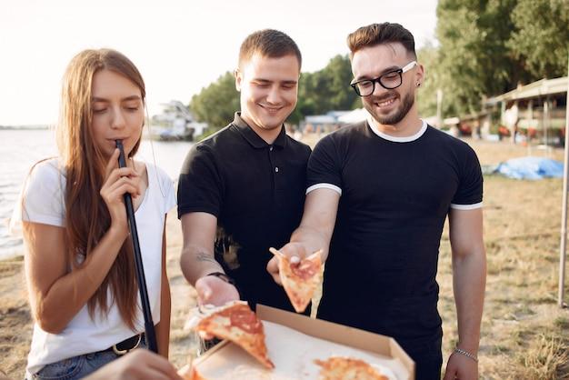 Молодые люди едят пиццу и курят кальян на пляже Бесплатные Фотографии