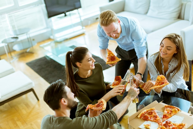 Young people eating pizza and drinking cider in the modern interior Premium Photo