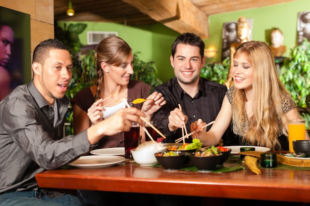 Young people eating in thai restaurant Premium Photo