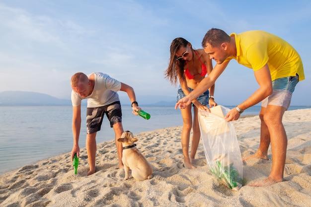 Giovani amici che raccolgono rifiuti e immondizia sulla spiaggia tropicale salvando il pianeta e l'ecologia in indonesia, thailandia e filippine Foto Gratuite
