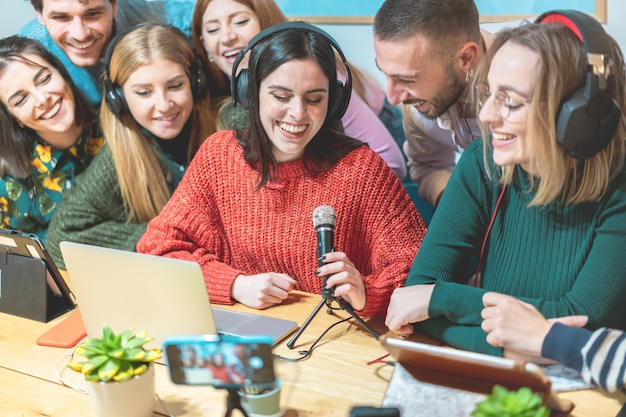 Young people friends streaming online in social network platform - contents creators making video feed interview - genration z and technology trends concept - focus on girl face wearing red jumper Premium Photo