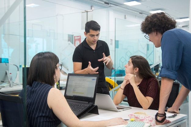 Young people gathered in a coworking discussing new marketing campaign. Premium Photo