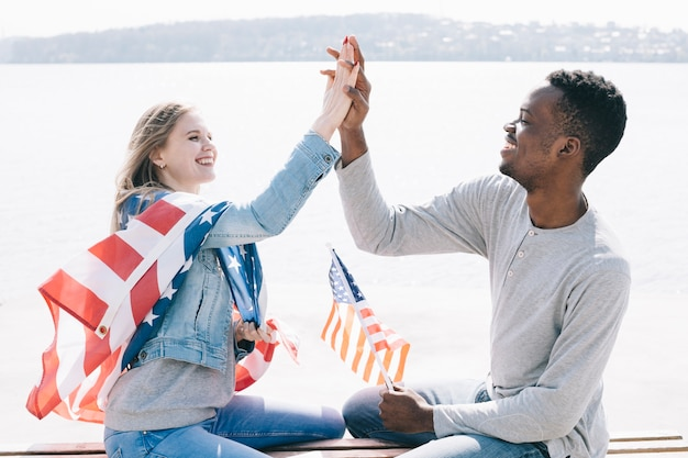 Young people giving high five while holding american flag Free Photo