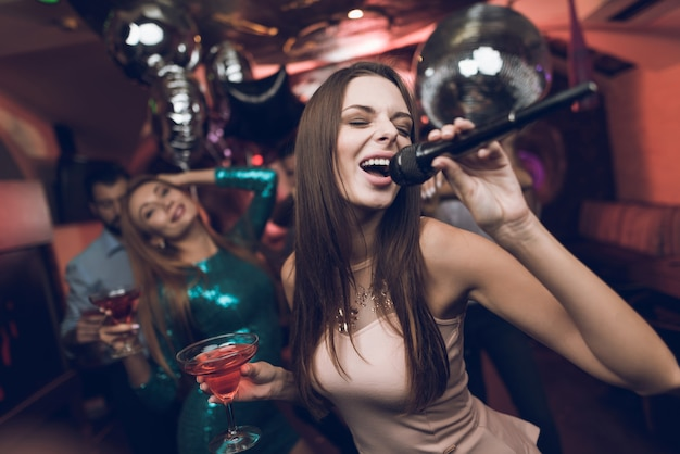 Young people have fun in a nightclub and sing in karaoke Premium Photo