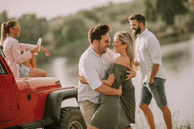 Young people having fun in convertible car by river Premium Photo