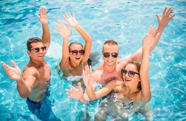 Young people having fun in swimming pool, smiling. Premium Photo