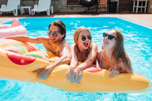 Young people holding a pizza swimming float Premium Photo