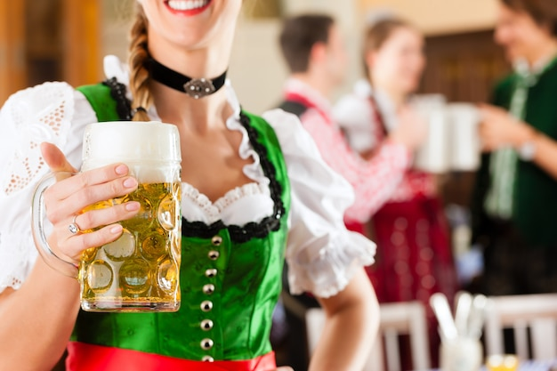 Молодые люди в традиционном баварском трахте в ресторане или пабе Premium Фотографии
