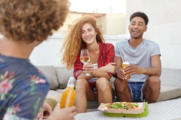 Молодые люди собираются вместе, сидя на удобном диване и интересно беседуя Бесплатные Фотографии