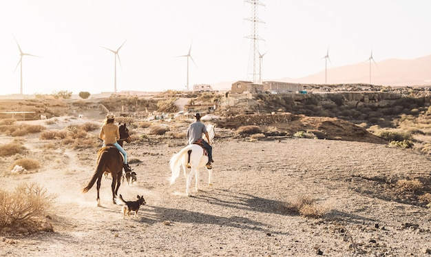 Young people riding horses in desert Premium Photo