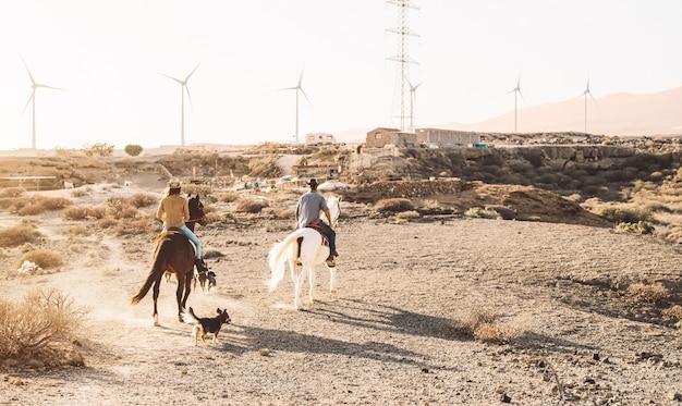砂漠で馬に乗る若者 Premium写真