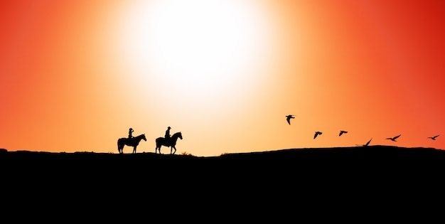 Young people riding horses at sunset time Premium Photo