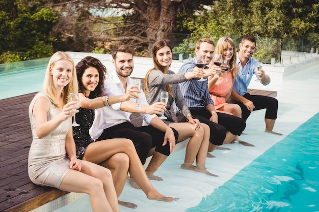 Young people sitting by swimming pool, drinking, having fun, enjoying holiday Premium Photo