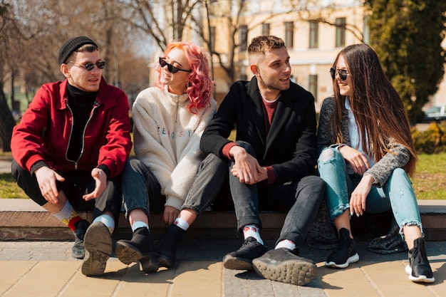 Young people sitting on curb and talking to each other Free Photo