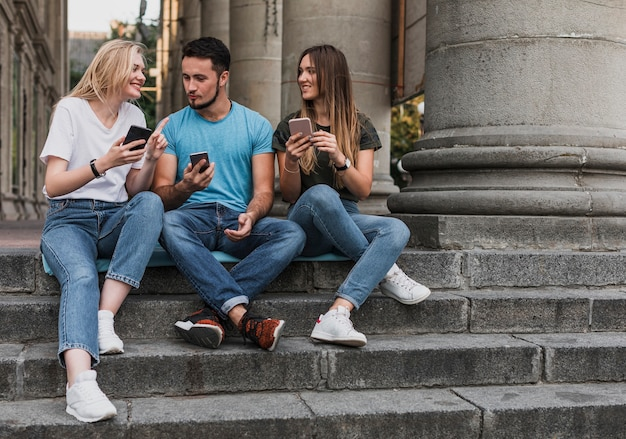 Young people sitting on stairs and checking their phones Free Photo