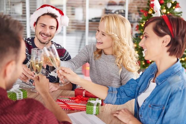 クリスマスパーティー中に乾杯する若者 無料写真