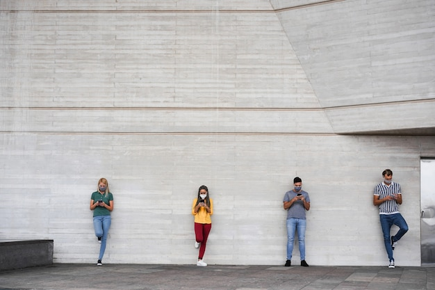 Young people wearing face safety masks using smart mobile phones while keeping social distance on coronavirus time Premium Photo