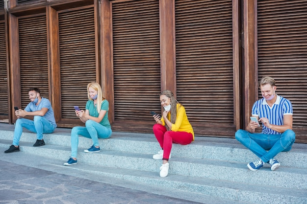 Young people wearing face safety masks using smart mobile phones while keeping social distance during coronavirus time Premium Photo