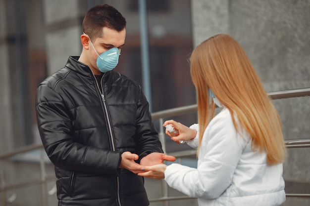 Young people wearing protective masks are spraying hand sanitizer Free Photo