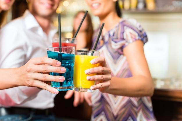 Молодые люди с коктейлями в баре Premium Фотографии
