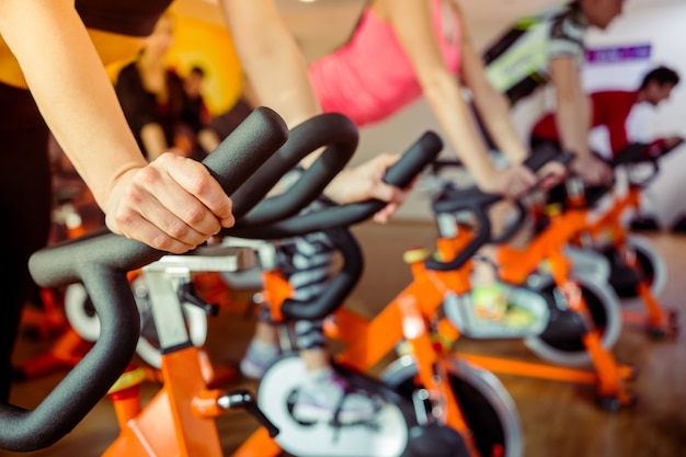 Young people working out on an exercise bike in gym. Premium Photo