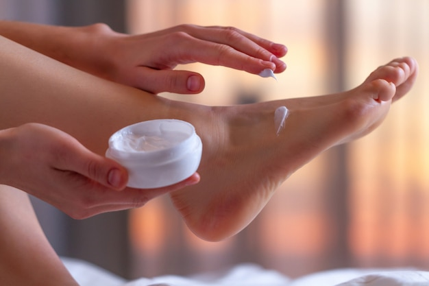 Young person caring about her feet and applying hydrating, moisturizing cream. foot and skin care. Premium Photo