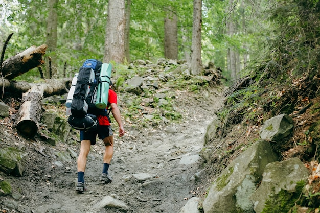 Young person hiking with a backpack in the forest Premium Photo